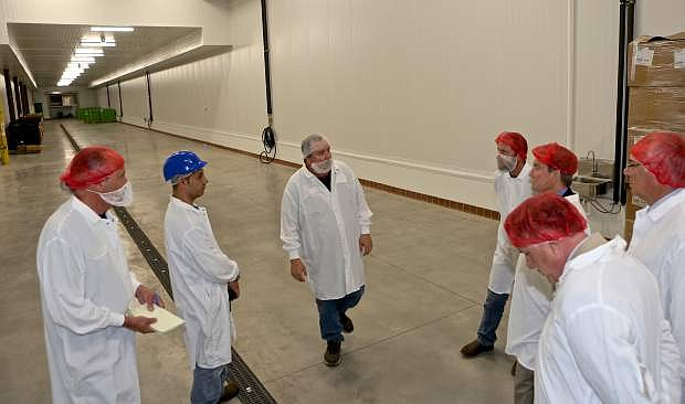 SunOpta Plant Manager John M. Stevens (center) tours city dignitaries and NNDA representatives through a safe food-handling area that will soon start producing for the company.