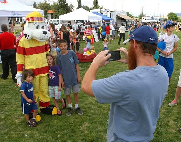 Trevor Rotoli snaps a picture of his children, Levino, 3, Sophia, 6, and Seth, 11, with Sparky at the National Night Out event on Tuesday.