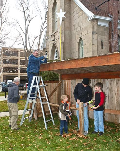 DeVere Henderson, Cal Hobson, Lucas Kordonowy, 6, Jake Kordonowy, 15, and Eric Mackay, 10, work on the manger for a living nativity at First United Methodist Church on Saturday.