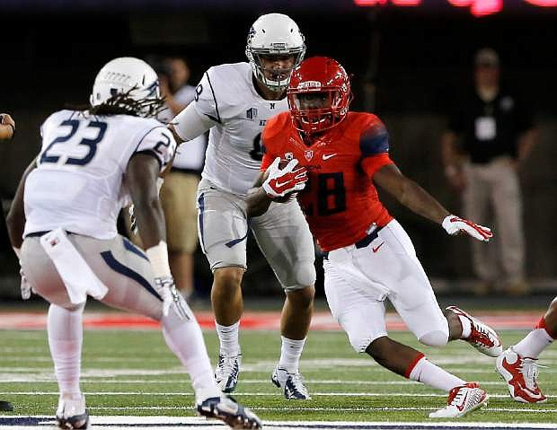Arizona running back Nick Wilson (28) rns between two Nevada defenders during the first half of the NCAA college football game, Saturday, Sept. 13, 2014, in Tucson, Ariz. (AP Photo/Rick Scuteri)