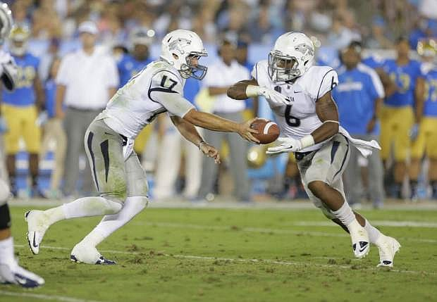 Nevada quarterback Cody Fajardo hands off to running back Don Jackson during the first half of an NCAA college football game against UCLA  in Pasadena, Calif., Saturday, Aug. 31, 2013. (AP Photo/Chris Carlson)