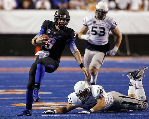 Boise State quarterback Grant Hedrick (9) runs the ball past Nevada linebacker Jordan Dobrich (49) during the first half of an NCAA college football game in Boise, Idaho, Saturday, Oct. 19, 2013. (AP Photo/Otto Kitsinger)