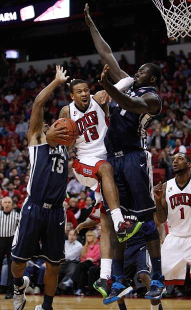 UNLV's Bryce Dejean-Jones tries for a shot against Nevada's D.J. Fenner, left, and Ali Fall, right, during an NCAA college basketball game Wednesday, Jan. 8, 2014, in Las Vegas. (AP Photo/Las Vegas Review-Journal, John Locher)