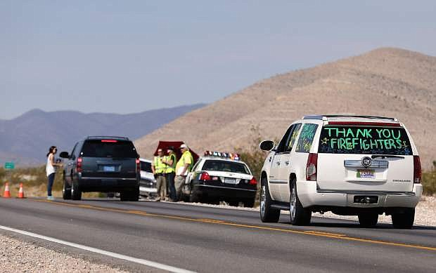 Motorists pass through a checkpoint on state route 157 returning to their homes in Kyle Canyon, Wednesday, July 17, 2013, near Las Vegas. Residents are heading back to mountain hamlets once threatened by a massive wildfire which began July 1, on Mount Charleston northwest of Las Vegas. Police were operating checkpoints for more than 400 people due to return to the Old Town, Rainbow and Echo communities in Kyle Canyon. (AP Photo/Julie Jacobson)
