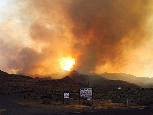 In this Friday, July 29, 2016 photo provided by Vince O'Daye, smoke and flames are visible from a wildfire burning in the community of Sutcliffe, Nev., about 35 miles north of Reno, Nev. The wildfire was deterred Sunday from burning the tribal town that had evacuated hundreds of residents. (Courtesy of Vince O'Daye via The AP)