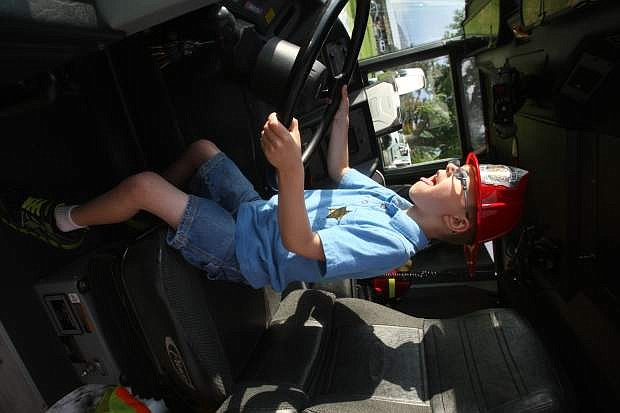 Dylan Reyes, 6, is thrilled to sit behind the wheel of a Carson City firetruck at the National Night Out community event on Tuesday.