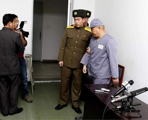 American missionary Kenneth Bae, right, leaves after speaking to reporters at Pyongyang Friendship Hospital in Pyongyang Monday, Jan. 20, 2014. Bae, 45, who has been jailed in North Korea for more than a year, appealed for the U.S. to do its best to secure his release. (AP Photo/Kim Kwang Hyon)