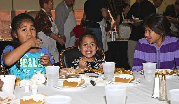 Sisters Natalie, 7, Emma Marie, 6, and LuLu Cervantes, 9, enjoy their Thanksgiving meal at the Nugget on Thursday.