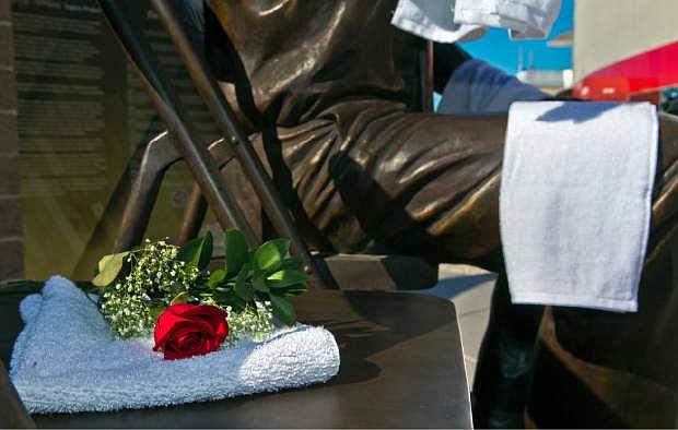 A rose and towels is left ar the Jerry Tarkanian statue near the Thomas & Mack Center in Las Vegas, Wednesday, Feb. 11, 2015. Hall of Fame coach Jerry Tarkanian, who built a basketball dynasty at UNLV but was defined more by his decades-long battle with the NCAA, died Wednesday, Feb. 11, 2015, in Las Vegas after several years of health issues. He was 84.(AP Photo/The Sunm L.E. Baskow) LAS VEGAS REVIEW-JOURNAL OUT