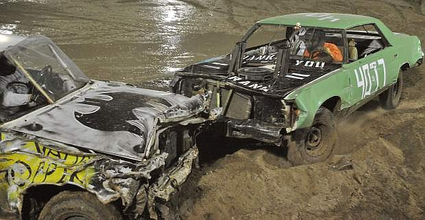 Laurence MItchell, left, is rammed while his casket is torn apart by father/competitor Randall Mitchell in the Demolition Derby on Friday night's fairgrounds events during Octane Fest.