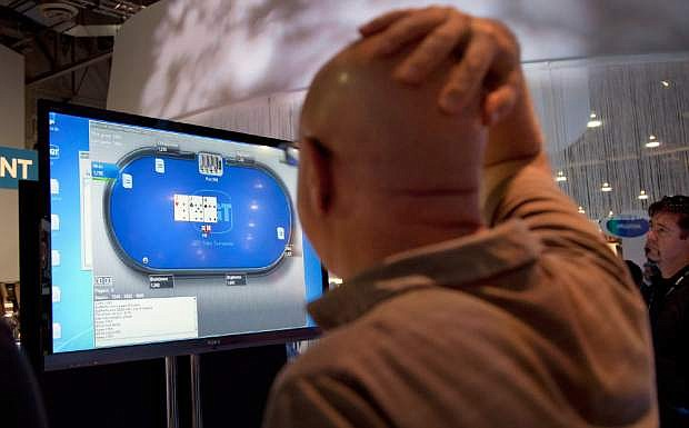 FILE - In this Oct. 4, 2011 file photo,  casino industry representatives and exhibitors watch an online poker game during industry's G2E conference in Las Vegas. Republican New York Congressman Peter King introduced legislation Thursday June 6, 2013, that would rescue online gambling from a legal gray zone and fully regulate it. The federal government cracked down on online poker in 2011, but that same year, the Justice Department issued a ruling making online gambling legal so long as it is permitted on the state level. (AP Photo/Julie Jacobson, File)