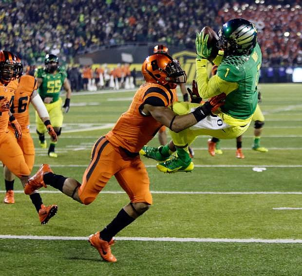 Oregon receiver Josh Huff, right, hauls in the winning touchdown against Oregon State defender Tyrequek Zimmerman  during the second half of an NCAA college football game in Eugene, Ore., Friday, Nov. 29, 2013. Oregon won 36-35. (AP Photo/Don Ryan)