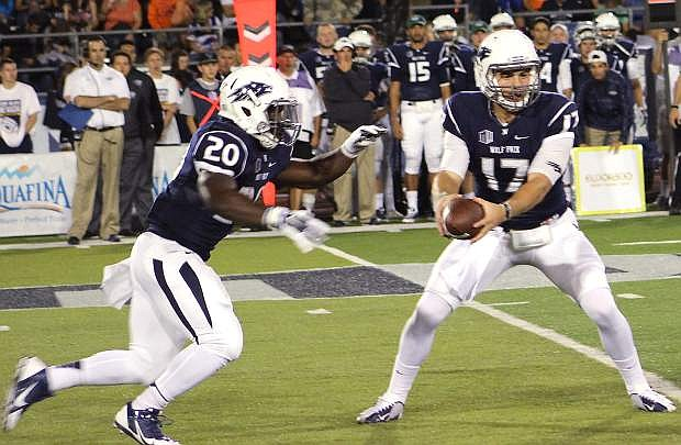 Nevada quarterback Cody Fajardo, right, hands off to James Butler during a game this year. The Wolf Pack hosts San Diego State on Saturday at Mackay Stadium in Reno.