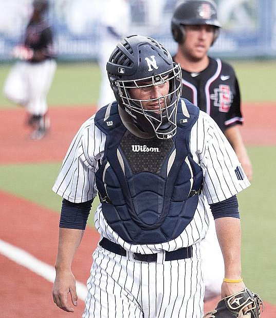 Nevada catcher Jordan Devencenzi looks to his dugout after San Diego State's Justin Wylie (back) hit a two-run homer to drive in teammate Spencer Thornton (behind) in the eighth inning on Friday.