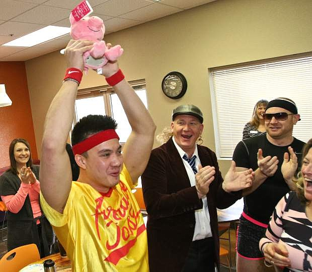 Greater Nevada's Jeff Copple is congratulated by his co-workers and competitors Wednesday while holding stuffed pig prize above his head.