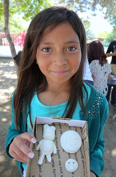 Victoria, 11, proudly displays her clay sculptures she created at the Art in the Park summer program on Monday.