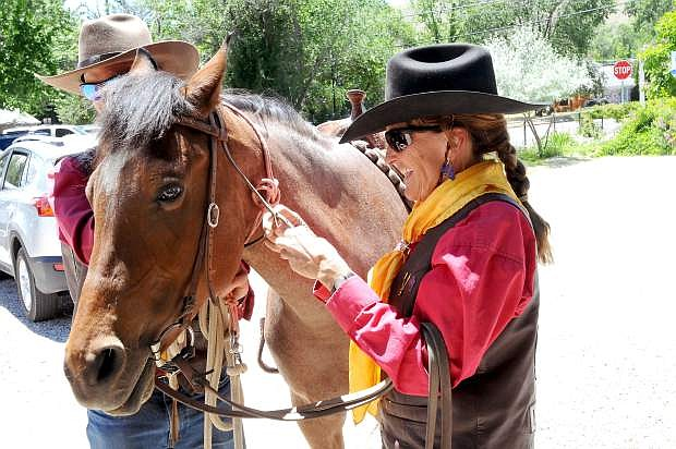 Anne Martin of Stagecoach gets ready to ride her Mustang, Rosie, on Thursday afternoon on Curry Street.