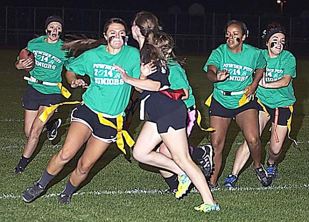 Junior running back Kyla Kincaid, left, follows the blocks of Miranda Ford, second from left, Courtney Cross and Nichole Mariezcurrena as senior Maddie Dirickson goes in for the tackle during the junior's 21-0 in the annual Powder Puff game on Monday.