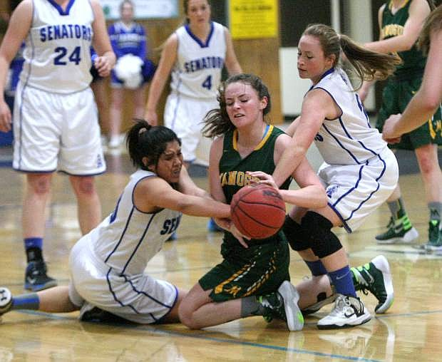 Brianna Alvarado and Melissa Glanzmann strip the ball from a Manogue player on Tuesday.