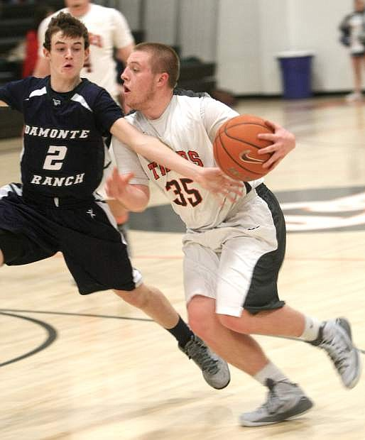 Douglas guard Trey Maurer drives to the basket past a Damonte Ranch defender on Tuesday night.