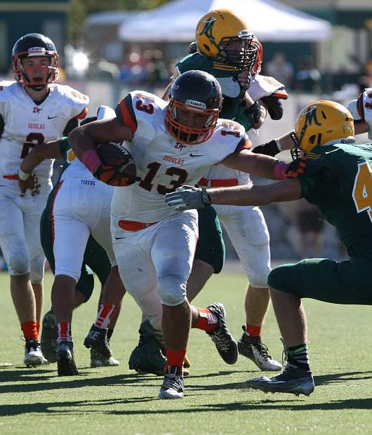 Douglas running back Kaleb Foster punches through the Manogue line on Saturday at Bishop Manogue HS in Reno. The Tigers lost 18-13.
