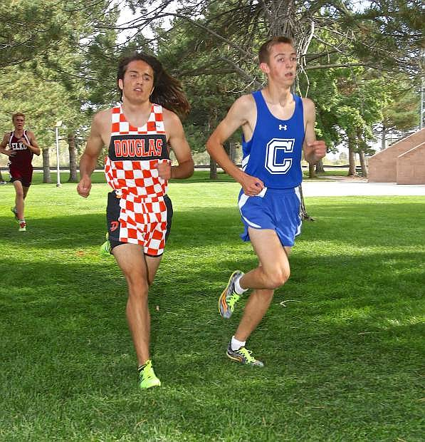 Douglas' Kaleb Morris and Carson's Ian Van Rensselaer battle on the first lap of the senior class race at Lampe Park in Gardnerville Friday. Van Rensselaer would leave Morris to finish 3rd.