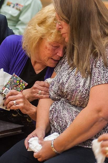 Peggy Eddington-Smith, 69, of Dayton, Nev., and Donna Gregory of St. Louis hug during a ceremony in Dayton, Nev., on Saturday, Sept. 21, 2013. Eddington-Smith's father, Pfc. John Eddington, died in World War II three weeks after her birth. A box of Eddington's personal items were discovered by Donna Gregory of St. Louis who traveled across the country to hand deliver the items to Eddington-Smith. (AP Photo/Kevin Clifford)