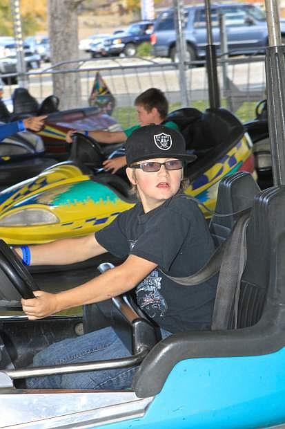 9-year-old Gabe Brackin looks for someone to run into on the bumper car ride at Mills Park Friday.