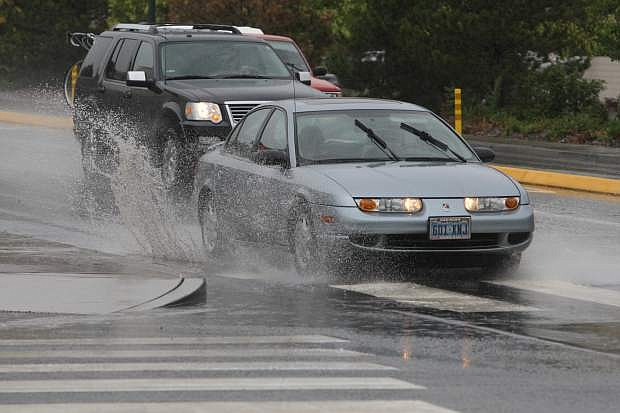 Motorists splash through a puddle at the intersection of Fairview Drive and Roop Street on Monday. More rain is in the forecast for today.
