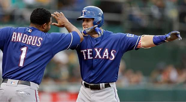 Texas Rangers' Ryan Rua, right, celebrates with Elvis Andrus (1) after hitting a home run off Oakland Athletics' Eric Surkamp during the third inning of a baseball game Tuesday, June 14, 2016, in Oakland, Calif. (AP Photo/Ben Margot)