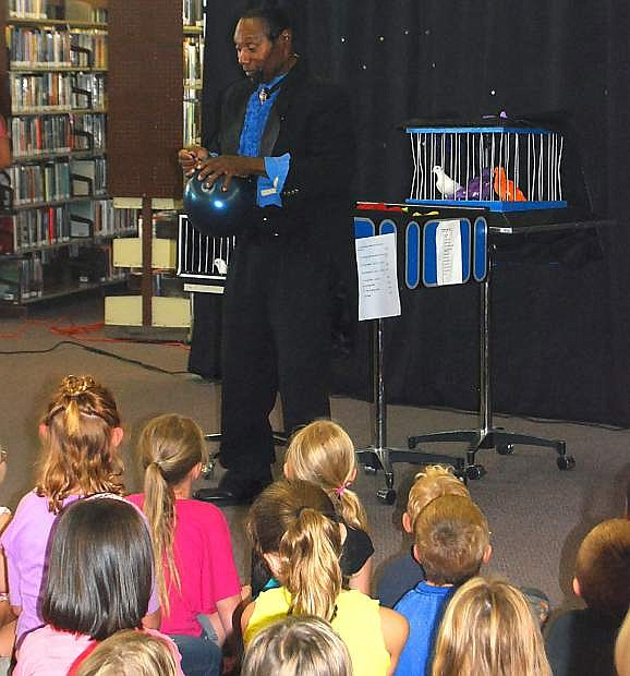 Wayne Ferguson from That's Magic Entertainment dazzles children during the library's summer reading program with magic that left the children in awe.