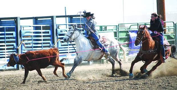 Rachel Hendrix, left, is shown with Aspyn Civil during team roping competition in 2012.