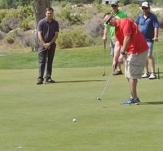 Chris Decker, red, puts on the green while his foursome watches quietly from behind.