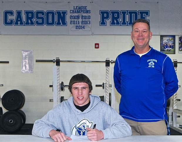 Kevin Rusler signs his national letter of intent to play football at William Penn University Wednesday at Carson High as Coach Blair Roman looks on.