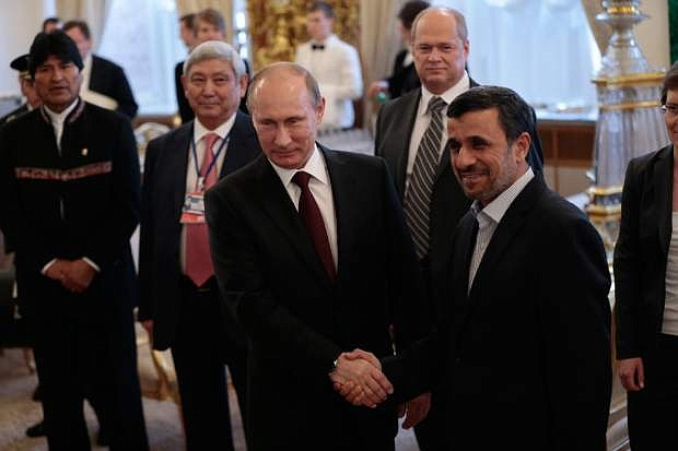 Russian President Vladimir Putin, center, and Iranian President Mahmoud Ahmadinejad shake hands at the Gas Exporting Countries Forum (GECF) in the Kremlin in Moscow, Monday, July 1, 2013. At left is Bolivia's President Evo Morales. (AP Photo/Ivan Sekretarev, Pool)