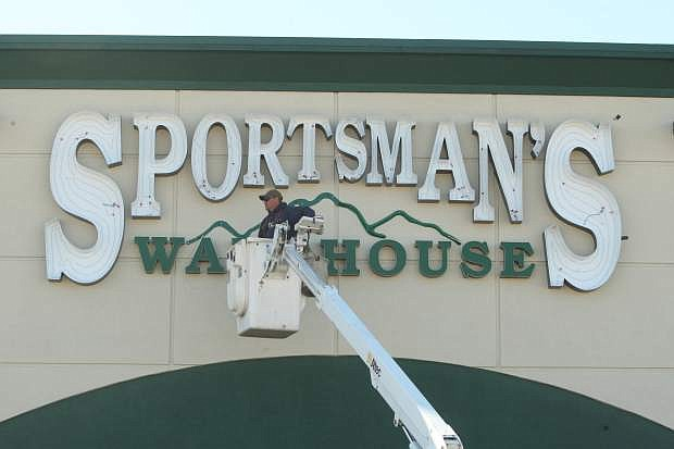Jeff Howser of YESCO installs neon tubing to the exterior Sportsman's Warehouse signage on Monday afternoon.
