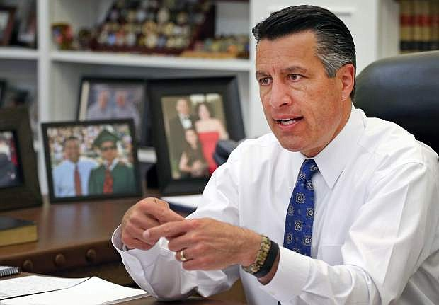 FILE - In this April 17, 2015 file photo, Nevada Gov. Brian Sandoval sits in his office at the Capitol in Carson City, Nev. Sandoval is pressing the Obama administration to alter its sage grouse protection plan to free up thousands of mining claims by shrinking the restricted area in exchange for making other unprotected areas off limits. (AP Photo/Cathleen Allison, File)