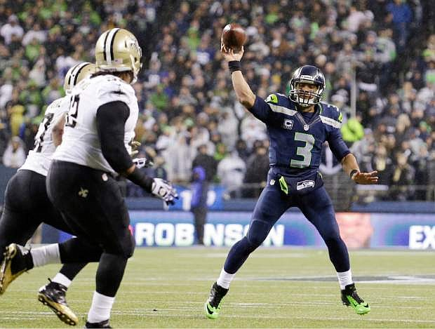 Seattle Seahawks quarterback Russell Wilson (3) throws against the New Orleans Saints in the first half of an NFL football game, Monday, Dec. 2, 2013, in Seattle. (AP Photo/Elaine Thompson)