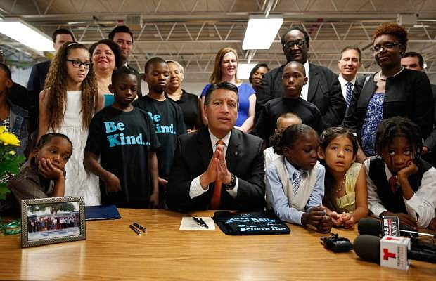 Nevada Governor Brian Sandoval, center, holds a bill signing ceremony Wednesday, June 3, 2015, in Las Vegas. The ceremony was for Senate Bill 432, which allocates millions of dollars for for low performing schools in the 20 poorest zip codes in Nevada. (AP Photo/John Locher)
