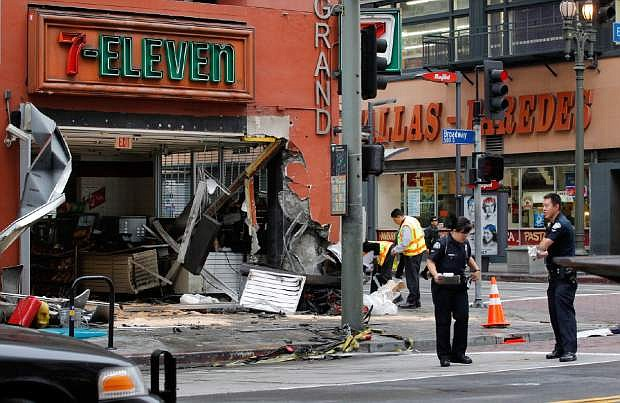 Los Angeles Police traffic officers investigate an accident involving a bus and a flatbed tow truck that collided sending the truck into a convenience store in downtown Los Angeles on Wednesday, June 12,2013. Fire Department spokeswoman Katherine Main says the collision before dawn critically injured a 35-year-old woman, seriously injured a 30-year-old man and caused minor injuries to a store employee. (AP Photo/Nick Ut)