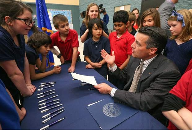 Nevada Gov. Brian Sandoval talks with a group of Carson City fifth-graders after signing into law an emergency bill extending bonds for school construction at a brief ceremony in Carson City, Nev., on Wednesday, March 4, 2015. More than a dozen lawmakers joined Sandoval for the signing of the bill which had bipartisan support in both houses. (AP Photo/Cathleen Allison)