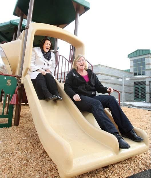 Mark Twain Elementary school principal Ruthlee Caloiaro, left, and kindergarten teacher Debi Crozier try out the new playground equipment installed for the kindergartners.