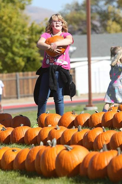 Eight-year-old Grace Billow, a third-grader at Seeliger, carries a pumpkin on Saturday during the school's annual pumpkin patch.