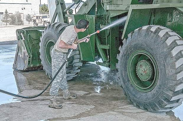 Staff Sgt. Brent Peden, a surface maintenance mechanic at the Combined Support Maintenance Shop in Carson City uses the new Net Zero Heavy Solids Wash Rack cannon to remove debris from a front loader before conducting a maintenance check.