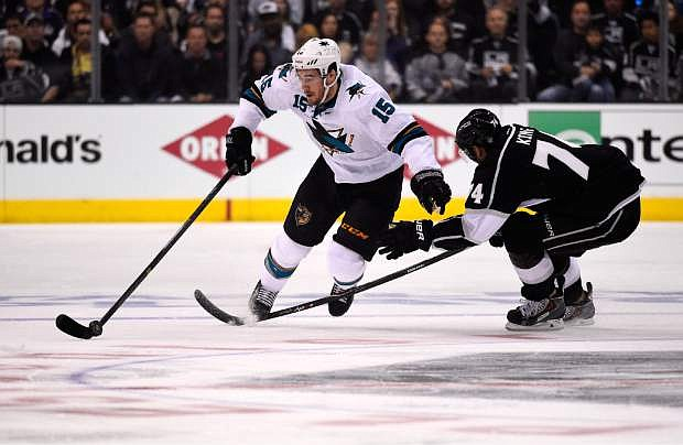 San Jose Sharks left wing James Sheppard, left, is tripped by Los Angeles Kings left wing Dwight King during the first period in Game 3 of an NHL hockey first-round playoff series , Tuesday, April 22, 2014, in Los Angeles. (AP Photo/Mark J. Terrill)