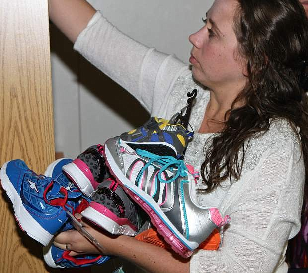 The Students in Transition program is looking for the public's help in acquiring more shoes for students in need. Samie Hefner is shown here stocking new shoes on Thursday.