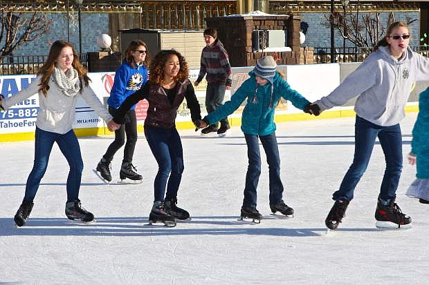 Rebekah Churchill, 16, Emerald Theriault, 15, Haley Funk, 13, and Katie Boogman, 12, all from Carson, form a human chain at the skating rink downtown on New Year's Day.