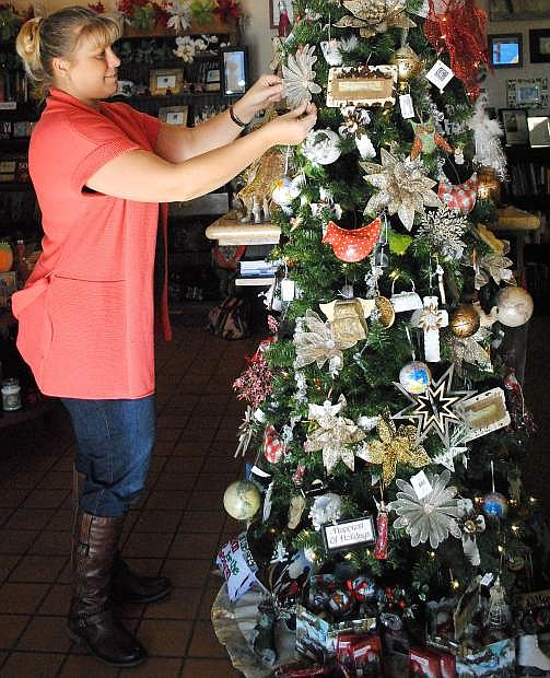 Wende Hook, owner of His Inspirations, is getting the store ready for Small Business Saturday by hanging Christmas ornaments.. Too Cute Totes and Blush Skin Spa and Boutique are also located in the same building.
