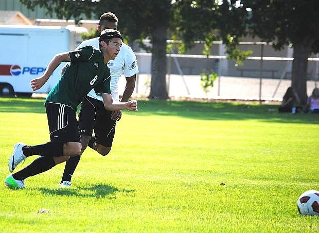 Fallon junior Corbin Waite, front, gets past a defender during the Wave's annual alumni soccer match on Wednesday at the Edward Arciniega Complex. Smoke from California wildfires has cancelled most of this week's practices and games.