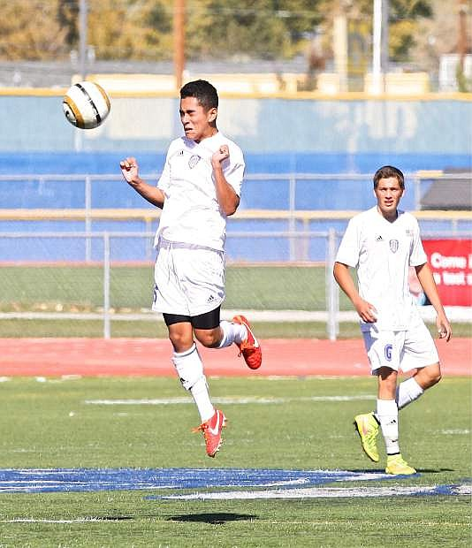 Carson midfielder Jose Sepulveda heads the ball while Peter Garrett looks on in a game against Wooster Saturday at home.